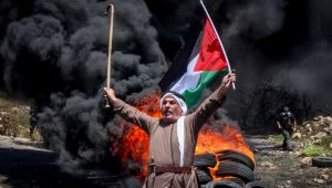 Palestinian protester stands in front of a pile of burning tires