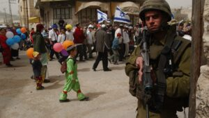 An Israeli soldier protects Jewish families as they celebrate Purim