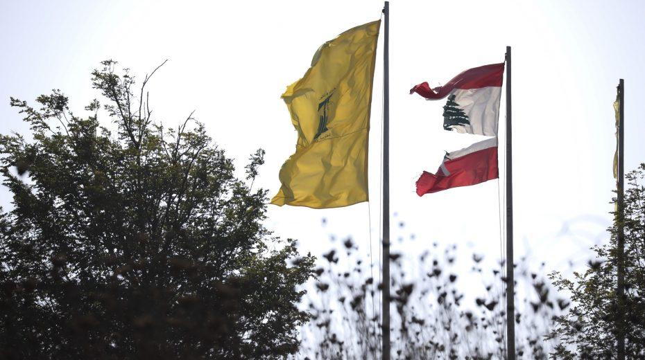 The flag of Lebanon torn and tattered alongside the flag of Hezbollah