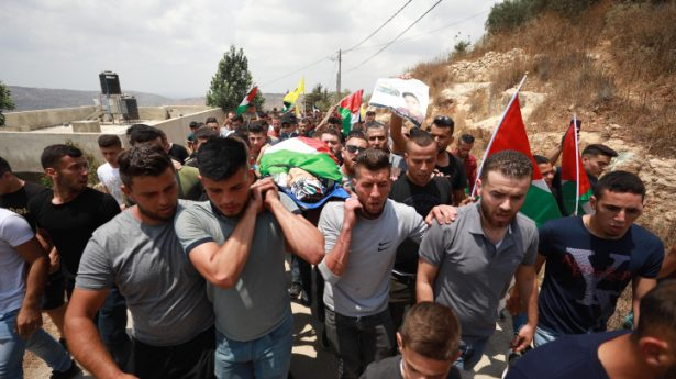 Palestinians carry the body of Mohammed Tamimi, 17, who was killed during clashes with Israeli security forces the previous day, during his funeral in the West Bank village of Deir Nizam, near Ramallah, July 24, 2021.
