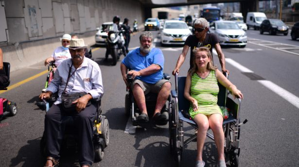Disabled, handicapped and activists block the Ayalon Highway in Tel Aviv as they attend a protest calling for better health care on July 25, 2021.
