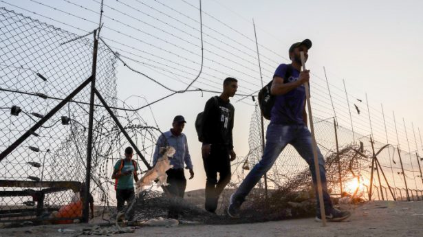 Palestinian workers cross into Israel through a hole in the security fence near the West Bank city of Hebron, July 25, 2021.
