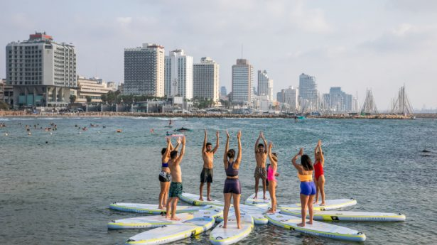 Israelis do yoga on sup (stand up paddle) boards, at a beach in Tel Aviv on August 26, 2021