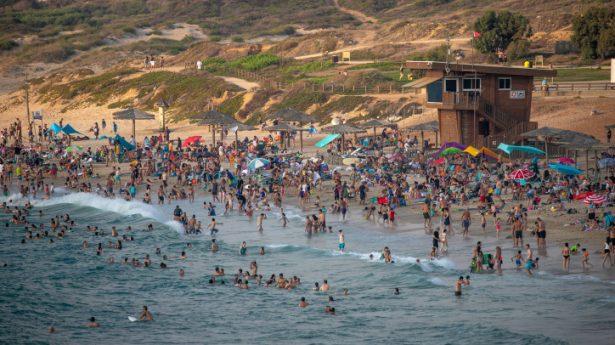 Israelis enjoy the Palmachim beach on August 21, 2021.