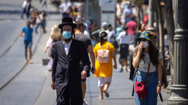 People walk some with face masks on Jaffa Street in Jerusalem, August 29, 2021.
