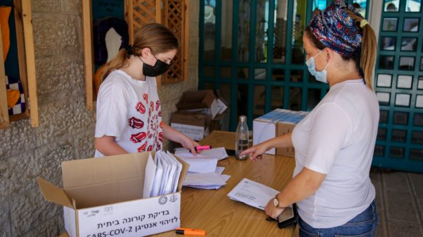 """Parents of children from """"Asa Hil"""" school receive Covid-19 home kit test ahead of the opening of the new school year in the Jewish settlement of Efrat, in Gush Etzion, August 29, 2021."""