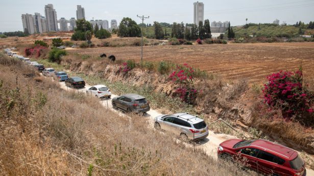 Cars stand in line waiting to enter a drive-through complex to check if they have been infected with the Coronavirus, in Rehovot on August 8, 2021.