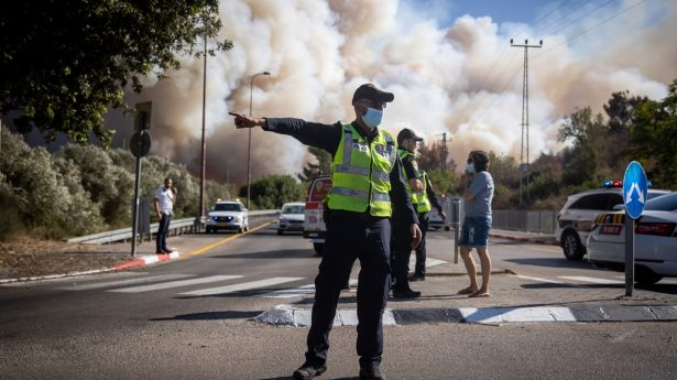 Police officers direct traffic away from a massive forest fire west of Jerusalem that burned over 17,000 dunams (over 4,200 acres) of land near the capital.